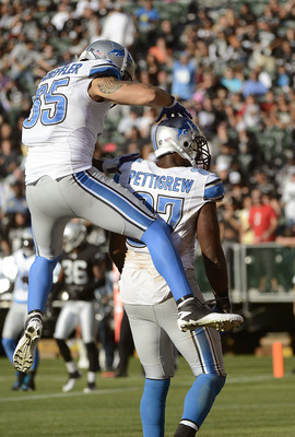 OAKLAND, CA - AUGUST 25:  Brandon Pettigrew #87 and Tony Scheffler #85 of the Detroit Lions celebrate after Pettigrew caught a seven yard touchdown pass against the Oakland Raiders in the third quarter of an NFL pre-season football game at O.co Coliseum o