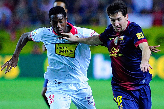 SEVILLE, SPAIN - SEPTEMBER 29:  Leo Messi (R) of FC Barcelona runs for the ball with Geoffrey Kondogbia (L) of Sevilla FC during the La Liga match between Sevilla FC and FC Barcelona at Estadio Ramon Sanchez Pizjuan on September 29, 2012 in Seville, Spain