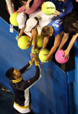 MELBOURNE, AUSTRALIA - JANUARY 22:  Novak Djockovic signs autographs for fans after his Quarterfinal match against Thomas Berdych of The Czech Republic during day nine of the 2013 Australian Open at Melbourne Park on January 22, 2013 in Melbourne, Austral