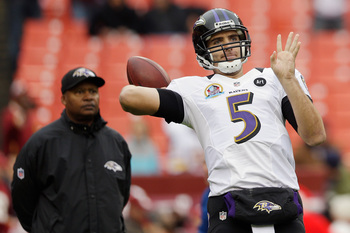 LANDOVER, MD - DECEMBER 09:  Quarterback Joe Flacco #5 of the Baltimore Ravens warms up as quarterbacks coach Jim Caldwell looks on prior to the start of the Ravens game against the Washington Redskins at FedExField on December 9, 2012 in Landover, Maryla