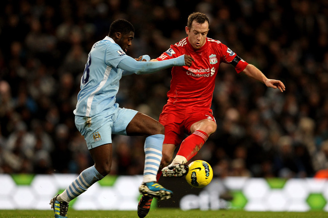 MANCHESTER, ENGLAND - JANUARY 03:  Charlie Adam of Liverpool competes with Kolo Toure of Manchester City during the Barclays Premier League match between Manchester City and Liverpool at the Etihad Stadium on January 3, 2012 in Manchester, England.  (Phot