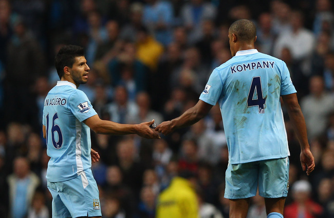 MANCHESTER, ENGLAND - OCTOBER 29:  Vincent Kompany of Manchester City walks off the pitch and hands team mate Sergio Aguero the captains arm band after being shown the red card during the Barclays Premier League match between Manchester City and Wolverham