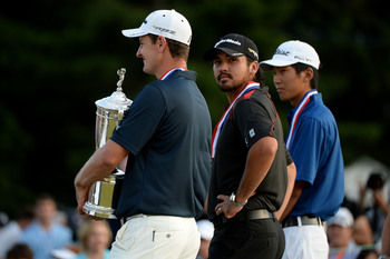 Jason Day looks on as Justin Rose holds the 2013 U.S. Open trophy.