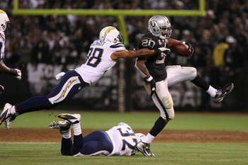 Marcus Gilchrist attempts to tackle Darren McFadden.