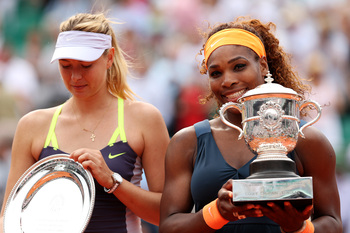Maria Sharapova looks at her runner-up trophy as Serena Williams beams after winning the 2013 French Open.