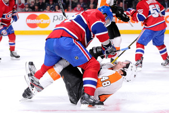 Then-Philadelphia Flyers forward Daniel Briere takes a cross-check.