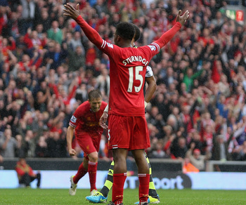 Sturridge celebrates his goal and awaits the incoming NFL-style tackle from his teammate.