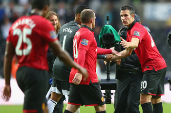 Shared moment: Rooney and Van Persie congratulate each other, but all is far from well.