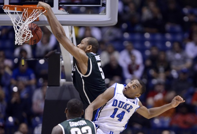 Mar 29, 2013; Indianapolis, IN, USA; Michigan State Spartans forward Adreian Payne (5) dunks over Duke Blue Devils guard Rasheed Sulaimon (14) in the second half during the semifinals of the Midwest regional of the 2013 NCAA tournament at Lucas Oil Stadiu