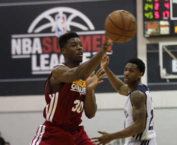 Jul 14, 2013; Las Vegas, NV, USA; Cleveland Cavaliers guard Carrick Felix passes the ball to a teammate as Memphis Grizzlies guard Gerald Robinson runs behind the play during an NBA Summer League game at Cox Pavillion. Cleveland won the game 69-58. Mandat