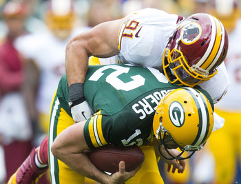 Sep 15, 2013; Green Bay, WI, USA;  Green Bay Packers quarterback Aaron Rodgers (12) is sacked by Washington Redskins linebacker Ryan Kerrigan (91) during the first quarter at Lambeau Field. Mandatory Credit: Jeff Hanisch-USA TODAY Sports