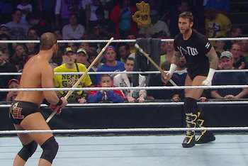 CM Punk and Curtis Axel begin the match wielding kendo sticks. Photo by: WWE