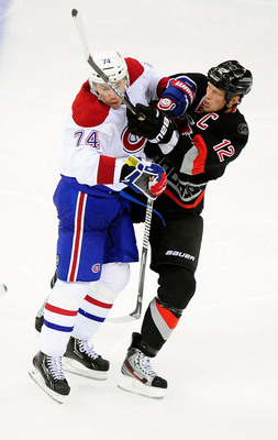 Montreal Canadiens defenseman Alexei Emelin hits Carolina Hurricanes captain Eric Staal.