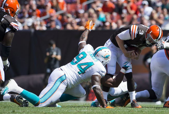 CLEVELAND, OH - SEPTEMBER 8: Defensive end Cameron Wake #91 and defensive tackle Randy Starks #94 of the Miami Dolphins sack quarterback Brandon Weeden #3 of the <a href=