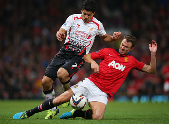 Hi-res-181804853-jonny-evans-of-manchester-united-tackles-luis-suarez-of_display_image