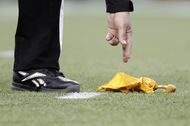 Hi-res-136194359-referee-reaches-down-to-pick-up-a-penalty-flag-during_crop_650