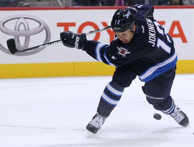 Hi-res-181960201-olli-jokinen-of-the-winnipeg-jets-misses-the-puck-as-he_crop_650