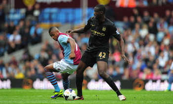 182104871-manchester-city-player-yaya-toure-holds-off-villa_display_image