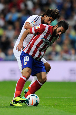 Hi-res-182143085-arda-turan-of-atletico-de-madrid-duels-for-the-ball_display_image