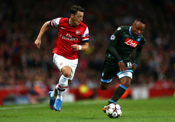 182603825-mesut-oezil-of-arsenal-goes-past-camilo-zuniga-of_display_image