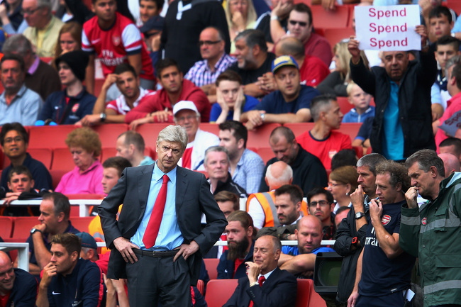 Hi-res-176691085-arsene-wenger-of-arsenal-looks-on-as-a-fan-behind-makes_crop_650