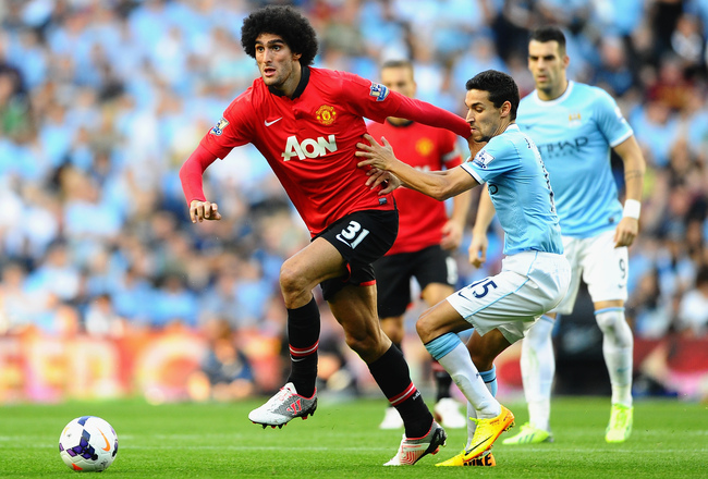 Hi-res-181548446-marouane-fellaini-of-manchester-united-holds-off-jesus_crop_650x440