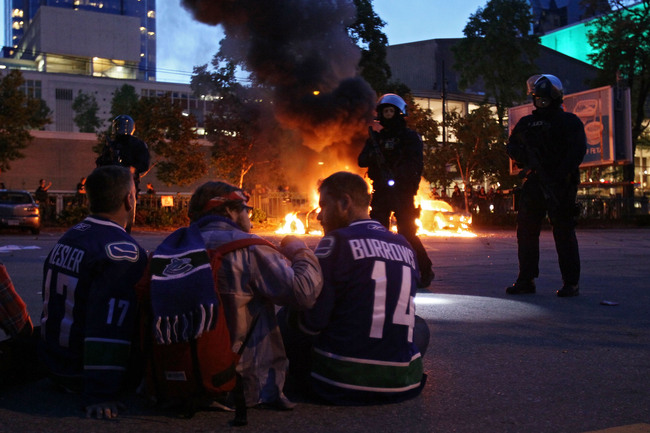 Hi-res-116458222-riot-police-stand-in-front-of-two-burning-police-cars_crop_650