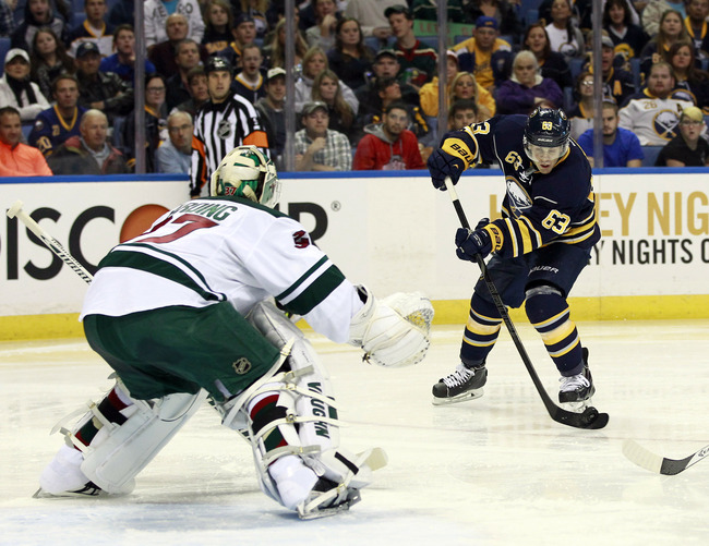 Oct 14, 2013; Buffalo, NY, USA; Buffalo Sabres left wing Tyler Ennis (63) shoots on Minnesota Wild goalie Josh Harding (37) during the second period at First Niagara Center. Mandatory Credit: Kevin Hoffman-USA TODAY Sports