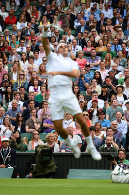 Roger Federer is a blur as he launches for a signature overhead, Wimbledon.