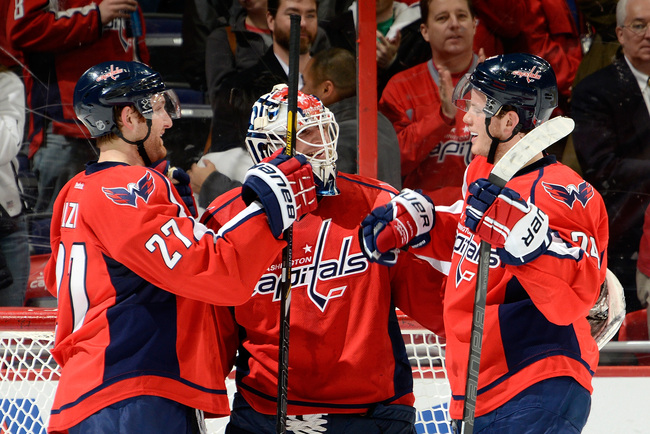 WASHINGTON, DC - FEBRUARY 26: Braden Holtby #70 of the Washington Capitals is congratulated by Karl Alzner (left) and John Carlson (right) after shutting out the Carolina Hurricanes at Verizon Center on February 26, 2013 in Washington, DC.  (Photo by Patr
