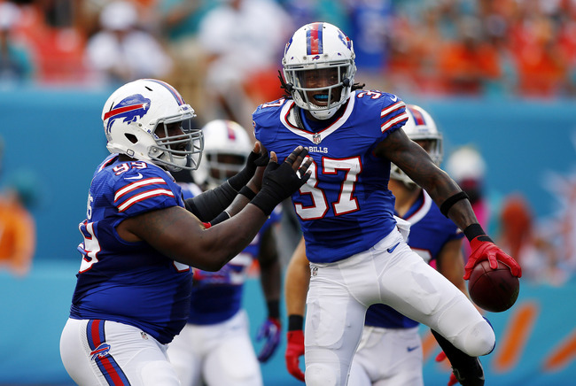 Oct 20, 2013; Miami Gardens, FL, USA; Buffalo Bills defensive back Nickell Robey (37) celebrates with  defensive tackle Marcell Dareus (99) after his interception for a touchdown against the Miami Dolphins in the first quarter at Sun Life Stadium. Mandato