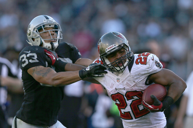 OAKLAND, CA - NOVEMBER 04: Doug Martin #22 of the Tampa Bay Buccaneers breaks free of Tyvon Branch #33 of the Oakland Raiders on his way turnover score a touchdwon at O.co Coliseum on November 4, 2012 in Oakland, California.  (Photo by Ezra Shaw/Getty Ima
