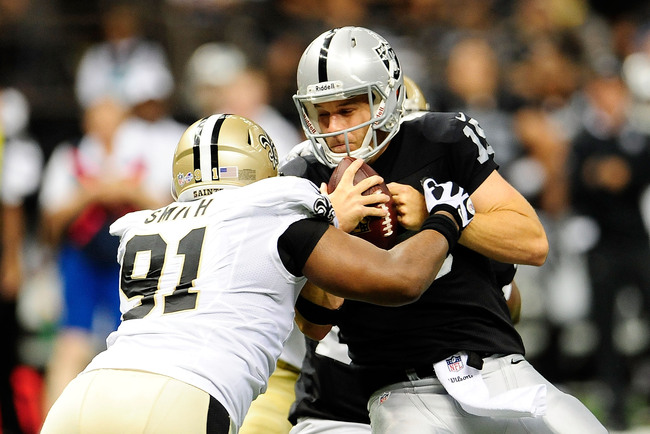 NEW ORLEANS, LA - AUGUST 16:  Matt Flynn #15 of the Oakland Raiders is sacked by Will Smith #91 of the New Orleans Saints during a preseason game at the Mercedes-Benz Superdome on August 16, 2013 in New Orleans, Louisiana.  (Photo by Stacy Revere/Getty Im