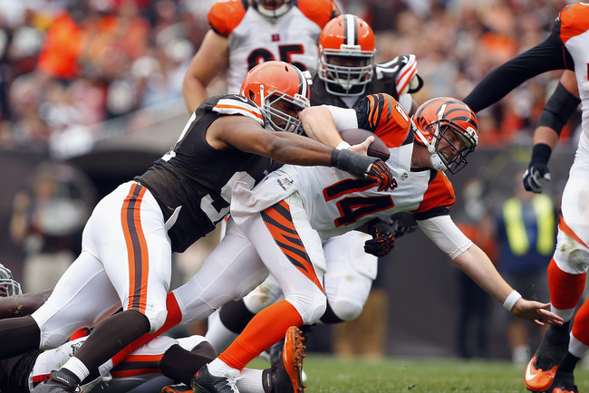CLEVELAND, OH - SEPTEMBER 29:  Quarterback Andy Dalton #14 of the Cincinnati Bengals is sacked by defenders Barkevious Mingo #51 and Ahtyba Rubin #71 of the Cleveland Browns at FirstEnergy Stadium on September 29, 2013 in Cleveland, Ohio.  (Photo by Matt
