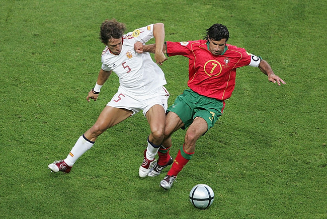 Hi-res-50979875-luis-figo-of-portugal-gets-tackled-by-carles-puyol-of_crop_650
