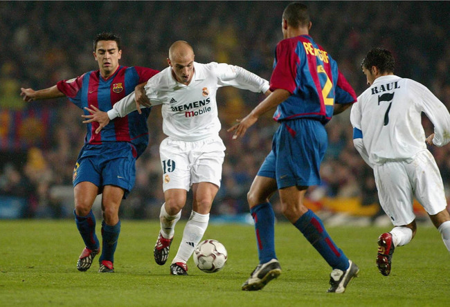 Hi-res-1658228-esteban-cambiasso-of-real-holds-off-hernandez-xavi-of_crop_650