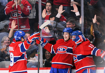 Montreal Canadiens Michael Bournival (left), Lars Eller and Brendan Gallagher celebrate a goal.