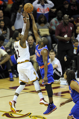 Kyrie Irving shooting over the finger tips of Raymond Felton