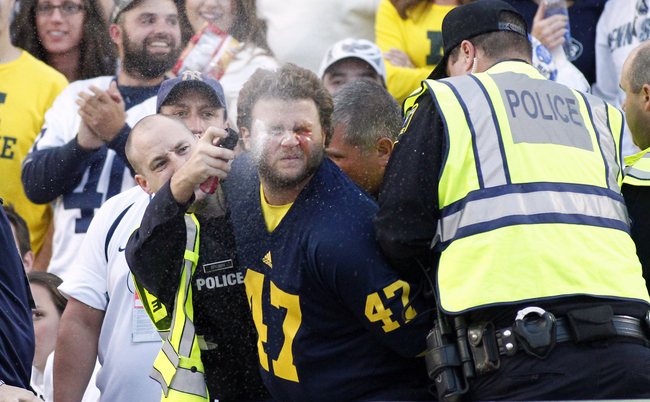Hi-res-184234969-michigan-wolverines-fan-is-maced-by-police-during-the_crop_650