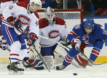 Montreal Canadiens goalie Peter Budaj with Habs forward Michael Bournival and New York Rangers forward Derick Brassard.