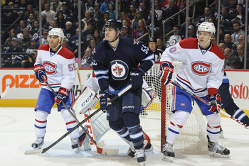 Montreal Canadiens defensemen Francis Bouillon (left) and Nathan Beaulieu (right) flanking Winnipeg Jets forward Mark Scheifele.