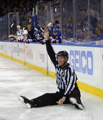 Hi-res-168193499-linesman-jean-morin-makes-a-first-period-icing-call_display_image