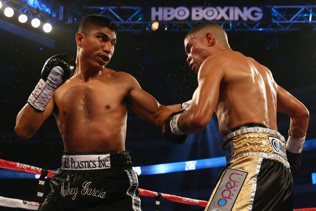 DALLAS, TX - JUNE 15:  (L-R) Mikey Garcia connects with a left to the face of Juan Manuel Lopez during their Vacant WBO Featherweight Title bout at American Airlines Center on June 15, 2013 in Dallas, Texas. Garcia knocked out Lopez in the fourth round.