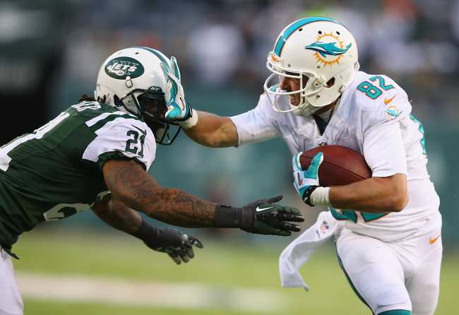 Hi-res-452795685-brian-hartline-of-the-miami-dolphins-stiff-arms-ellis_crop_650