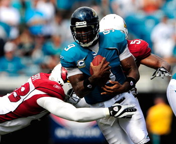 JACKSONVILLE, FL - SEPTEMBER 20:  David Garrard #9 of the Jacksonville Jaguars is tackled by Karlos Dansby #58 of the Arizona Cardinals during the game at Jacksonville Municipal Stadium on September 20, 2009 in Jacksonville, Florida.  (Photo by Sam Greenw