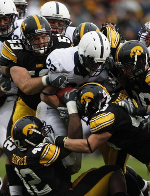 IOWA CITY, IA - NOVEMBER 8:  Defenders Matt Kroul #53, Pat Angerer #43 and Jeremiah Hunter #42 of the Iowa Hawkeyes tackle Evan Royster #22 of the Penn State Nittany Lions as he rushes for yards in the second quarter of play at Kinnick Stadium on November