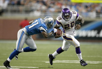 DETROIT - SEPTEMBER 20:  Running back Adrian Peterson #28 of the Minnesota Vikings carries the ball past cornerback Rhillip Buchanon #31 of the Detroit Lions at Ford Field on September 20, 2009 in Detroit, Michigan. The Vikings won 27-13.  (Photo by Steph