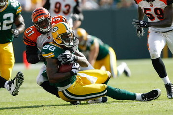 GREEN BAY, WI - SEPTEMBER 20: Tight end Jermichael Finley #88 of the Green Bay Packers is tackled by defensive back Roy Williams #31 of the Cincinnati Bengals at Lambeau Field on September 20, 2009 in Green Bay, Wisconsin. The Bengals defeated the Packers