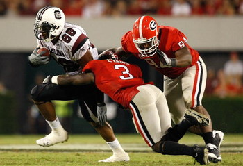 ATHENS, GA - SEPTEMBER 12:  Weslye Saunders #88 of the South Carolina Gamecocks breaks a tackle by Bryan Evans #3 and DeAngelo Tyson #94 of the Georgia Bulldogs at Sanford Stadium on September 12, 2009 in Athens, Georgia.  (Photo by Kevin C. Cox/Getty Ima