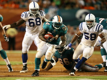 MIAMI - SEPTEMBER 21: Running back Ricky Williams #34 of the Miami Dolphins looks for room to run after getting past linebacker Gary Brackett #58 of the Indianapolis Colts at Land Shark Stadium on September 21, 2009 in Miami, Florida. The Colts defeated t